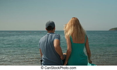 Young couple sitting on shore on sunny day. Man hugs his...