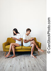Young couple sitting on sofa back to back using mobile phones