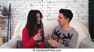 young couple sitting on sofa looking at each other with glasses in hands