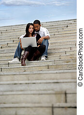 Young couple sitting on steps with a laptop