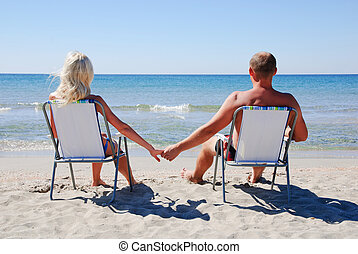 Young couple sitting on the beach chair on the sea beach and...