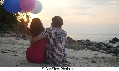 Young couple sitting on the beach hugging with balloons look sunset. slow motion. 1920x1080