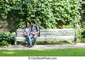 Young couple sitting on the bench with a cup of coffee