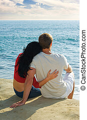 young couple sitting on the bluffs overlooking the Pacific ...