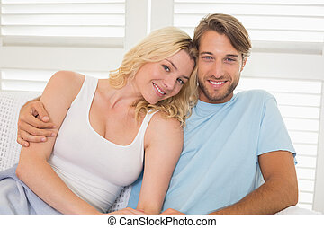 Young couple sitting on the couch smiling at camera