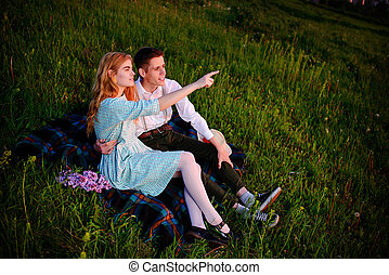 young couple sitting on the plaid in the park and look at the sunset, Woman is pointing to the horizon