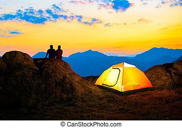 Young Couple Sitting on the Rock near Illuminated Tent and Watching the Beautiful Evening Mountain View with Sunset Sky