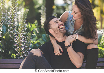 Young couple sitting together outside laughing