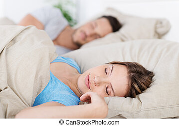 Young couple sleeping in bed having a restful sleep, closeup...
