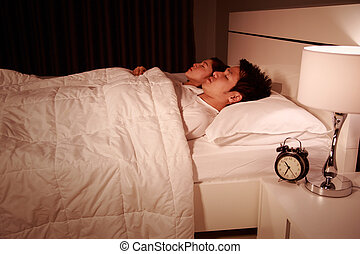 couple sleeping on a comfortable bed in bedroom at night