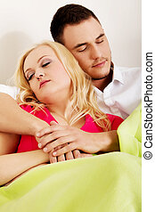 Young couple sleeping on the sofa under blanket