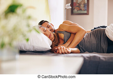 Young couple sleeping soundly in bed together