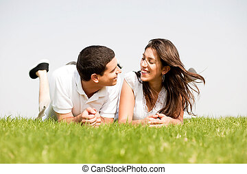 young couple smiling by laying down in a green grass field