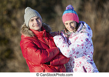 Young couple smiling, looking at the camera in winter