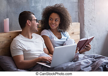 Young couple smiling to each other in bed