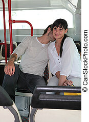Young couple smooching on a bus