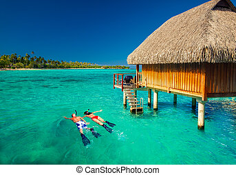 Young couple snorkling from hut over tropical lagoon - Young...