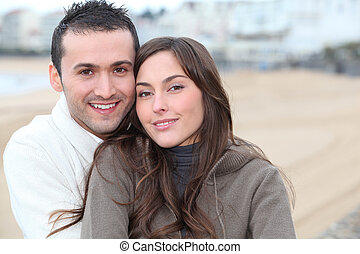 Young couple spending a week-end at the beach in winter