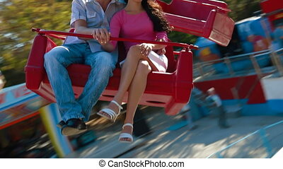 Young couple spinning on a carousel