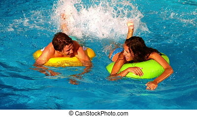 Young couple splashing and having f