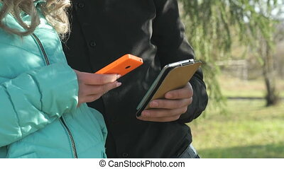 Young couple stand and hold the mobile phones in the park