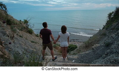 Young couple stand by shore and look at sea in summer day...