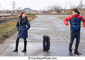 Young couple standing arguing in the road