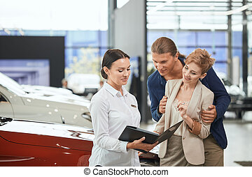 Positive young couple standing at the car dealership , getting know car features from sales rep female.
