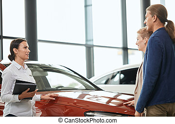 Sales rep telling about discount programme, standing at the car dealership in front of business couple.
