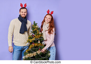 Young couple standing by Christmas tree