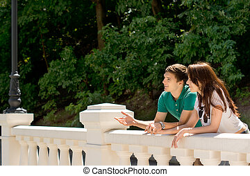 Young couple standing chatting on a bridge
