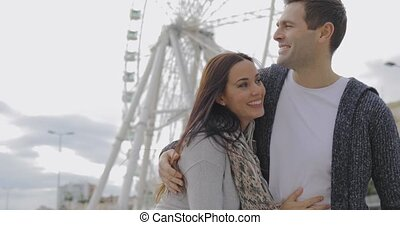 Young couple standing in front of a ferris wheel looking up...