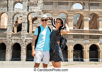 Young Couple Standing In Front Of Colosseum