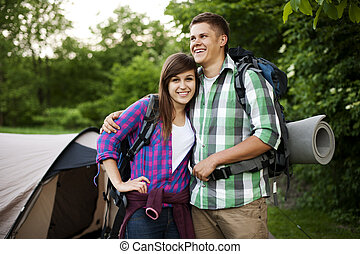 Young couple standing in front of tent
