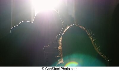 Young couple standing near window embracing talking and the sun shines through the window with lense flare effects.
