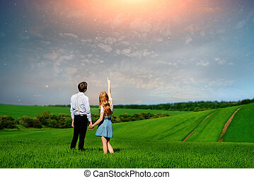 Young couple standing on green field, woman showing her hand at the stars