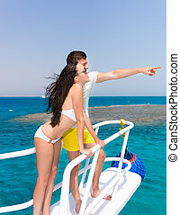 Young couple standing on the nose of the yacht at a sunny summer day, boy indicate by hand