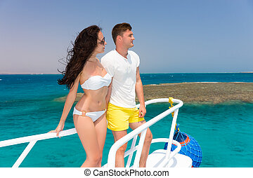 Young couple standing on the nose of the yacht at a sunny summer day