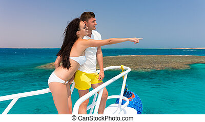 Young couple standing on the nose of the yacht at a sunny summer day, girl indicate by hand