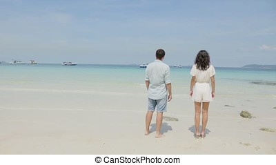 Young couple standing on wet sand by sea and looking to a blue sky. A beautiful young woman holds her handsome partner as they watch the sunset together on a romantic beach. Summer holidays