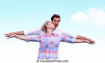 Young couple standing with arms outstretched