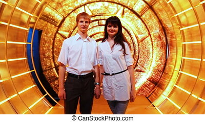 couple stands holding hands in fabulous decoration tunnel -...