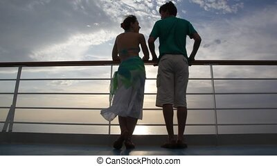 couple stands on deck of cruise ship and talks