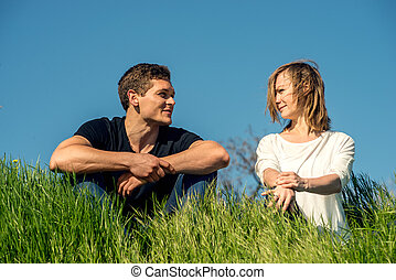 Young couple stitting on a grass - Young couple standing on ...