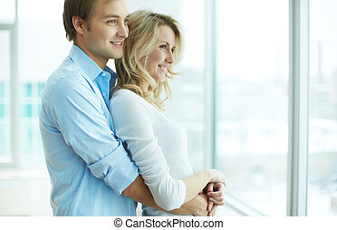 Young couple - Image of young guy embracing his girlfriend...