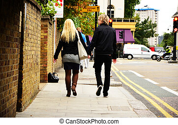 Young Couple - A young couple is walking on the street,...