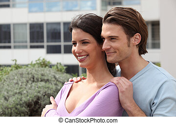 Young couple stood outside building