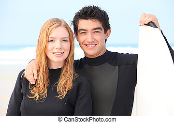 Young couple stood with surfboard