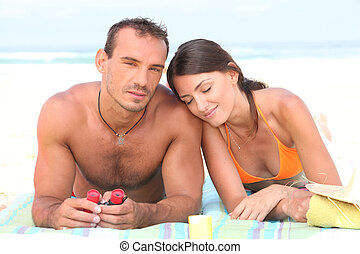 Young couple sunbathing on the beach