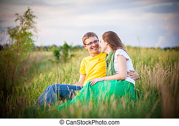 young couple sunset, green field